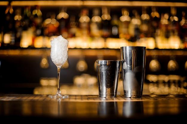 Verre rose vintage rempli de glace et de shaker en acier sur le comptoir du bar