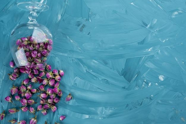 Verre de roses violettes séchées dispersées sur fond bleu.