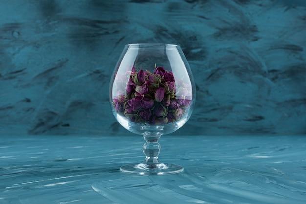 Verre de roses violettes séchées placé sur une surface bleue.