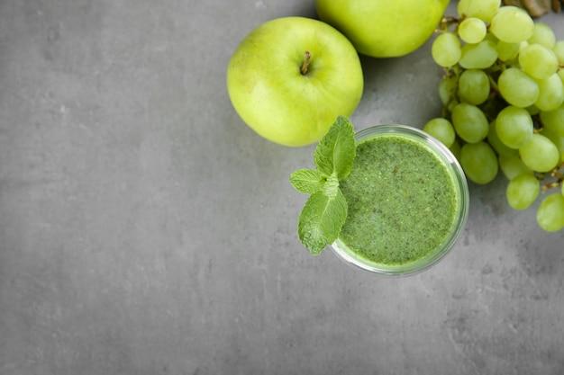 Verre de savoureux smoothie à l'avocat et fruits frais sur table