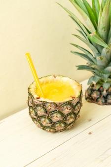Verre à smoothie d'ananas frais sur une table en bois