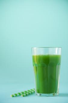Verre de smoothie au céleri vert sur fond bleu