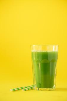 Verre de smoothie au céleri vert sur fond jaune