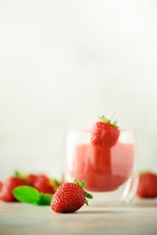 Verre avec smoothie aux fraises végétalien sur fond gris avec espace de copie.