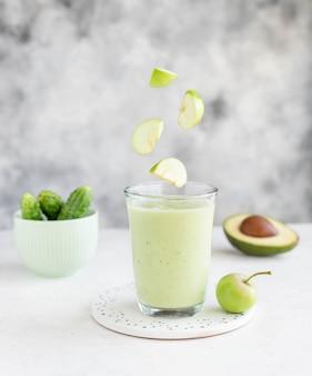 Verre de smoothie avec avocat, concombre et pommes