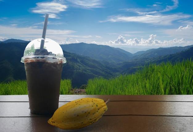Verre de smoothie de cacao sur le fond des montagnes et du ciel bleu