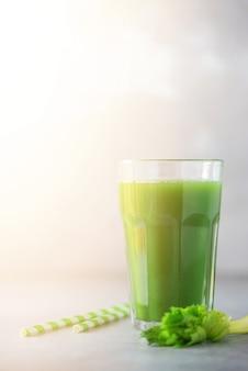 Verre de smoothie de céleri vert sur fond de béton gris