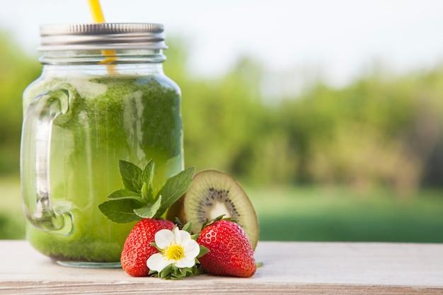 Verre de smoothie détox et de fruits sur une table en bois dans le jardin avec des fruits