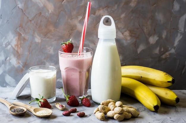 Un verre de smoothie fraise-banane parmi les ingrédients nécessaires à sa préparation