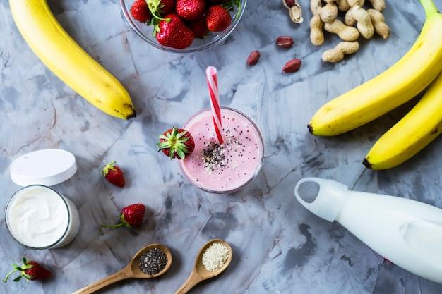Un verre de smoothie fraise banane parmi les ingrédients pour sa cuisine