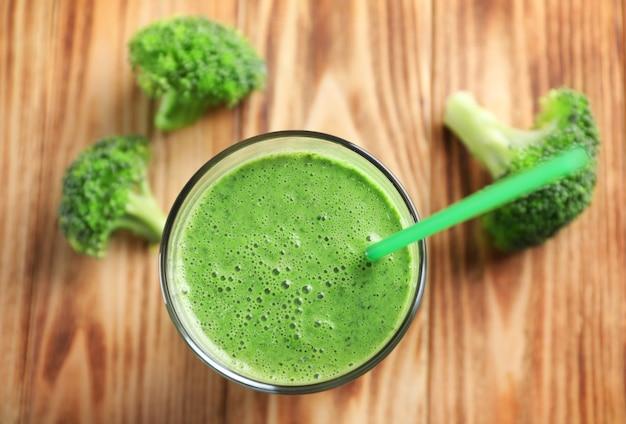 Verre de smoothie de légumes frais sur table en bois