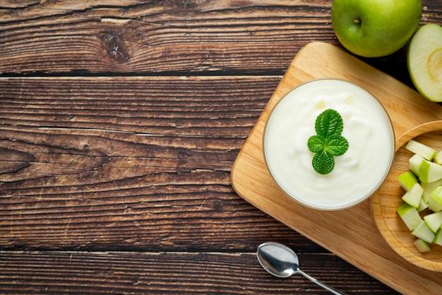 Verre de smoothie sain de pomme verte mis à côté de pommes vertes fraîches