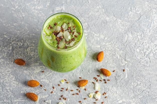 Verre avec smoothie vert d'épinards avocat céleri kiwi et lait de coco