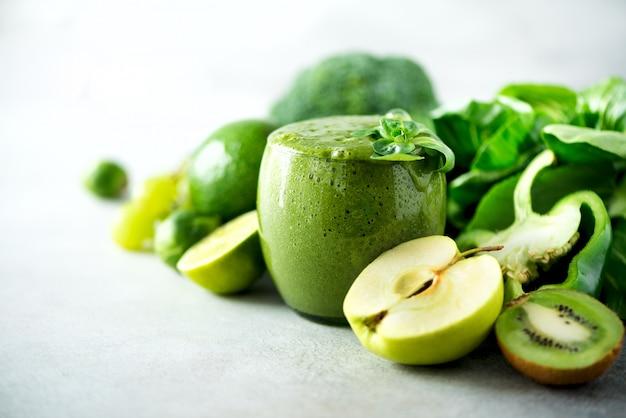 Verre avec smoothie vert, feuilles de chou frisé, citron vert, pomme, kiwi, raisin, banane, avocat, laitue.