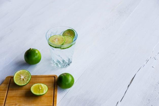 Un verre de soda, citron et citron vert sur la table