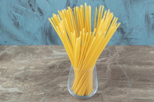 Verre de spaghettis à tubes non cuits sur une surface en marbre