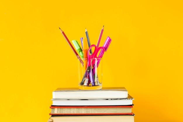 Un verre avec des stylos, des crayons et des ciseaux sur une pile de livres pour la formation