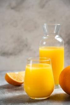 Un verre de tasses de jus d'orange et de tranches d'orange.