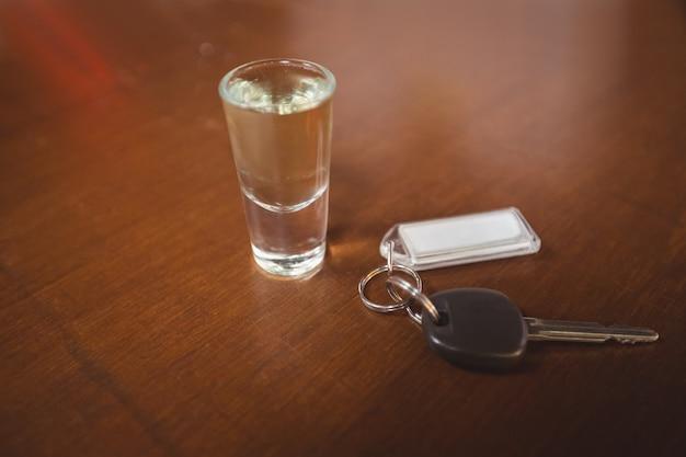 Verre de tequila tourné avec clé de voiture dans le comptoir du bar