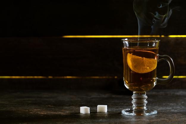 Verre de thé au citron sur une vieille surface en bois