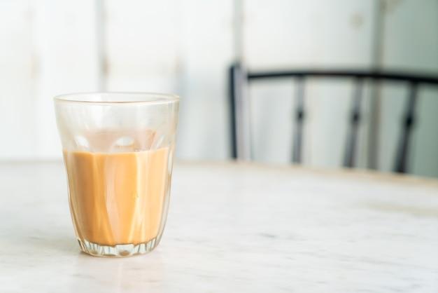 Verre de thé au lait thaï chaud sur table