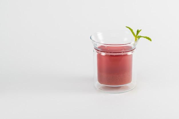 Un verre de thé aux fruits et une feuille de menthe sur fond blanc, isolé
