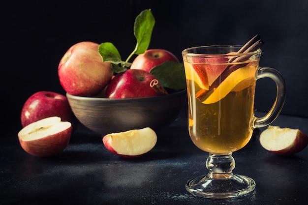 Verre de thé aux pommes chaud au citron et à la cannelle sur tableau noir. automne nature morte.