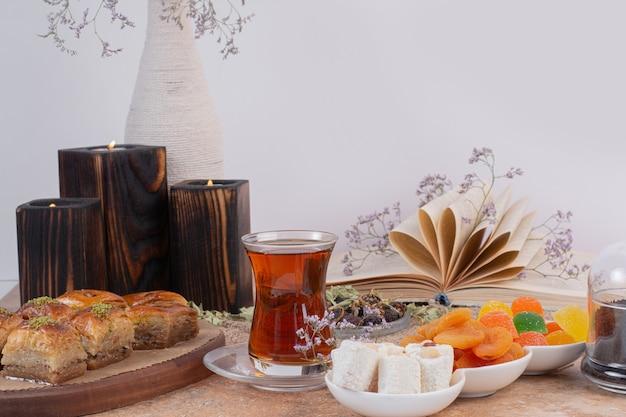 Verre de thé, bonbons et divers baklavas traditionnels sur table en marbre.