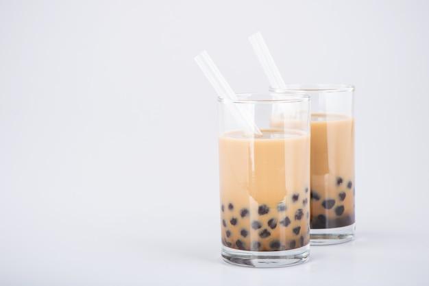 Un verre de thé à bulles au lait sucré avec des perles de tapioca et de la paille sur fond blanc. copier l'espace