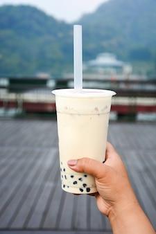 Verre de thé à bulles de lait avec des perles de tapioca en main touristique avec fond de lac soleil lune