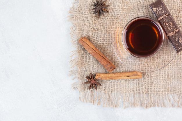 Verre de thé, cannelle et chocolat sur toile de jute