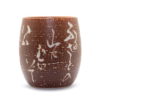 Verre à thé en céramique de style japonais au centre de l'image sur fond blanc