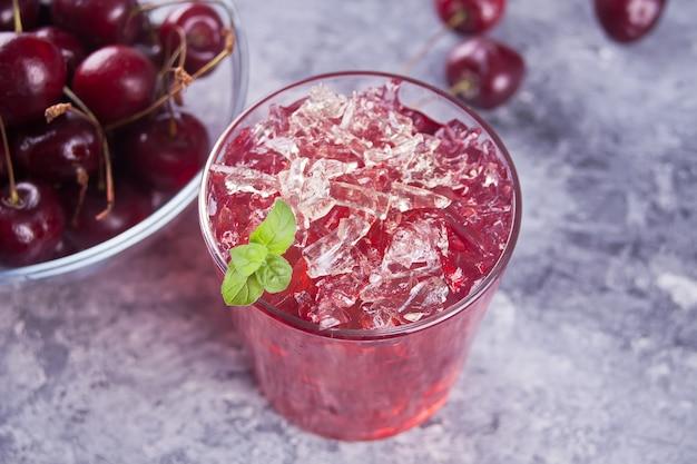 Verre de thé ou de cocktail glacé à la cerise fraîche et faite maison, limonade à la menthe. boisson rafraîchissante. fête d'été.