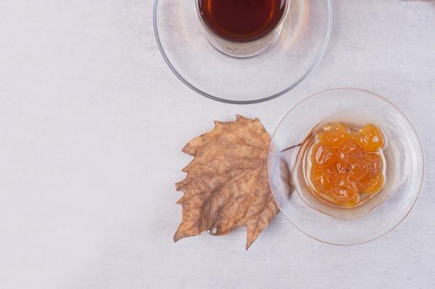 Verre de thé et confiture de baies sur une surface blanche.
