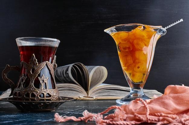 Un verre de thé avec une confiture de cerises.
