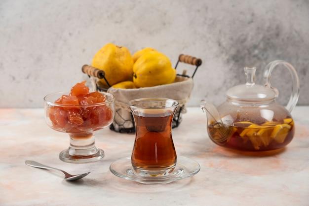 Verre de thé, confiture et coings sur plaque de bois.