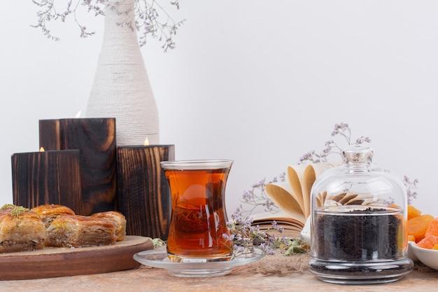 Verre de thé et divers baklavas traditionnels sur table en marbre.