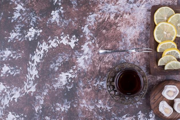 Un verre de thé avec du lokum et des tranches de citron