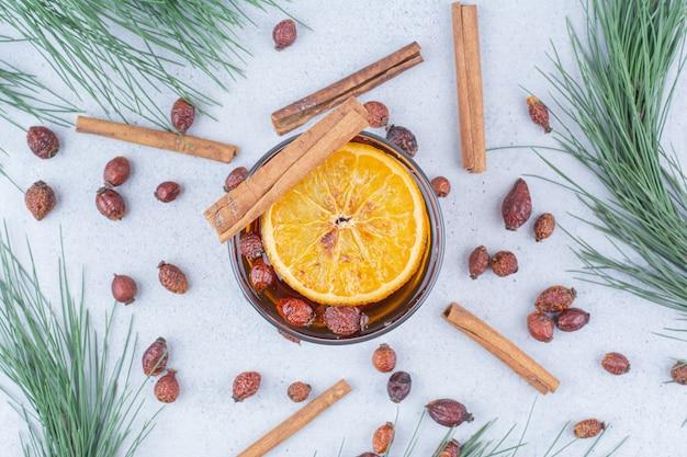 Verre de thé à l'églantier et cannelle sur une surface en marbre.
