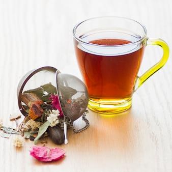 Verre de thé avec feuilles sèches