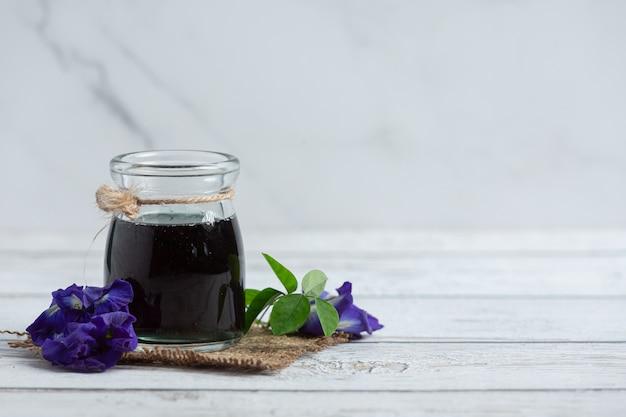 Verre de thé de fleur de pois papillon mis sur plancher en bois blanc