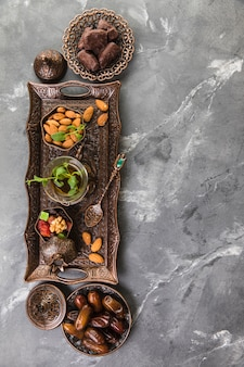 Verre à thé avec fruits de dattes et amandes sur plateau