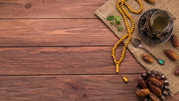 Verre à thé avec fruits de dattes et perles sur toile