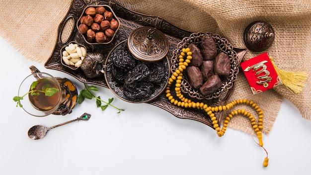 Verre à thé avec fruits secs et perles sur toile