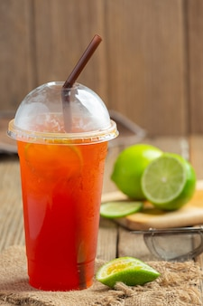 Verre à thé glacé au citron avec miel et citron sur un mur en bois.