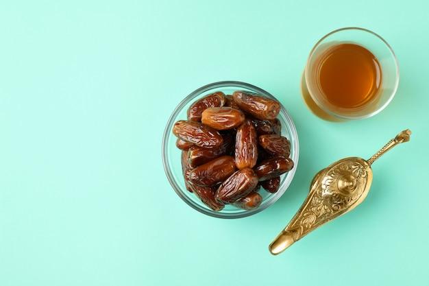 Verre de thé, lampe ramadan et dattes sur surface menthe