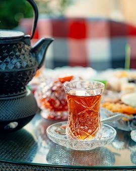 Un verre de thé noir avec une bouilloire noire en fer.