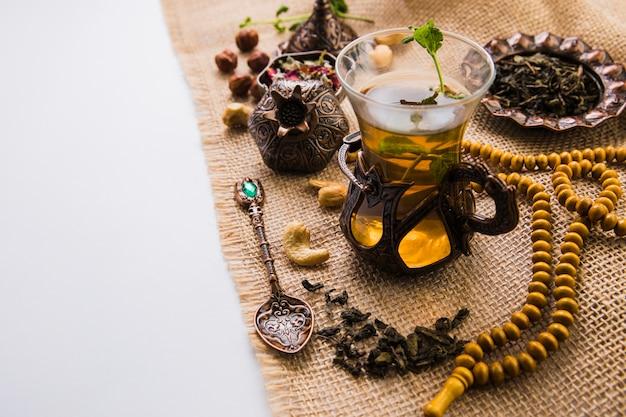 Verre à thé avec noix, herbes et perles sur toile