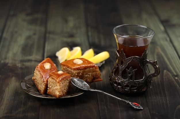 Un verre de thé avec pakhlava caucasien et citron sur une table rustique.