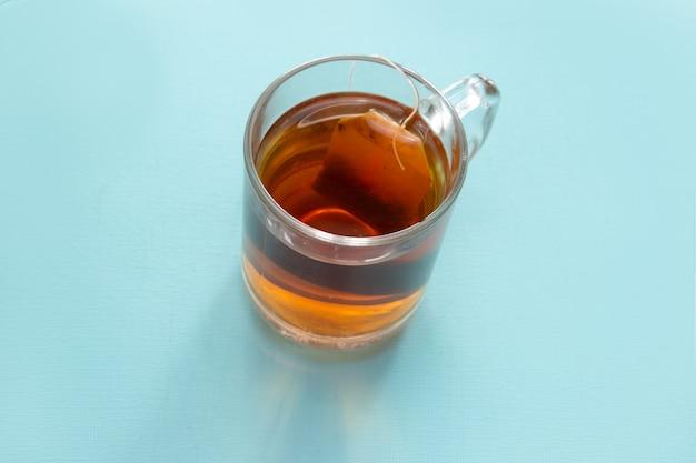 Verre de thé avec un sachet sur fond bleu